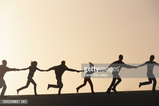 Silhouette of people running hand in hand : Stockfoto