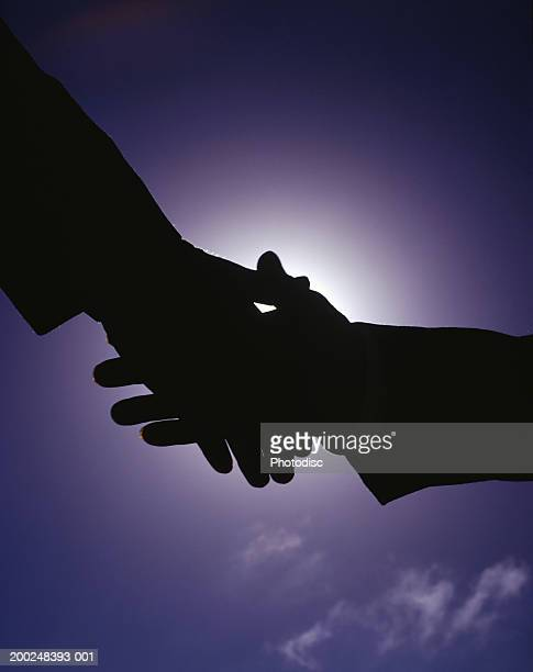 Silhouette of people shaking hands, Close-up of hands, , (Close-up)