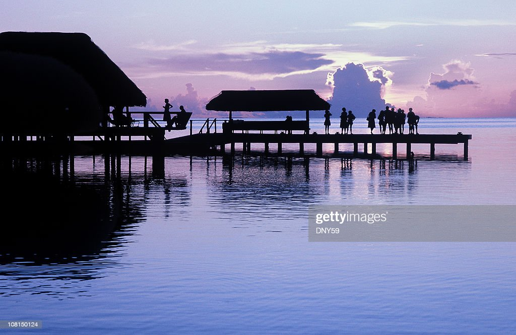 Silhouette of People Standing on Pier Watching Sunset : Foto stock