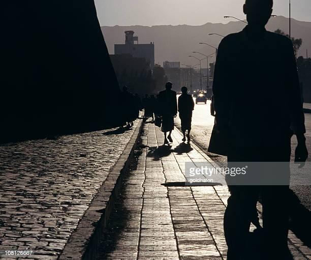 Silueta de personas caminando por la acera