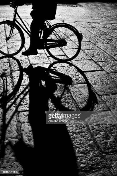 Silhueta da pessoa Bicyling do paralelepípedo rua. Preto e Branco
