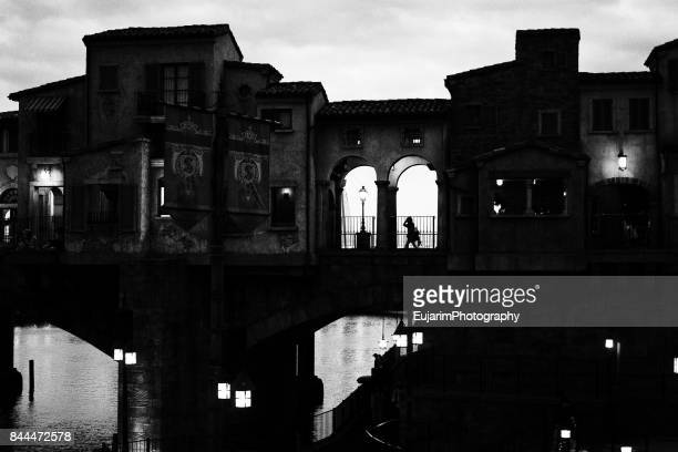 Silhouette of person crossing a medieval style covered bridge