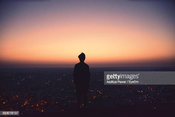 Silhouette Of Person Looking At City View From Observation Point At Sunrise