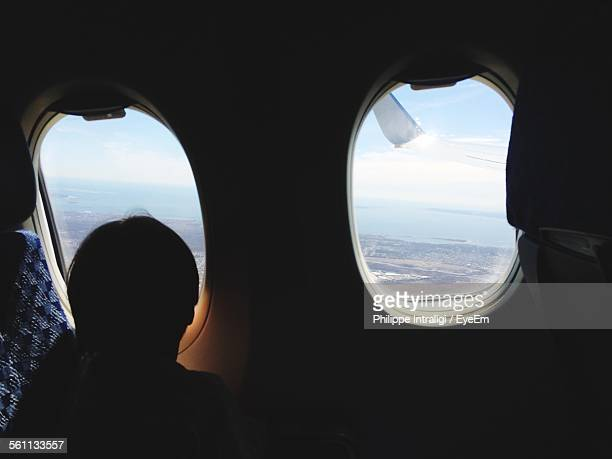 Silhouette Of Person Looking Through Airplane Porthole