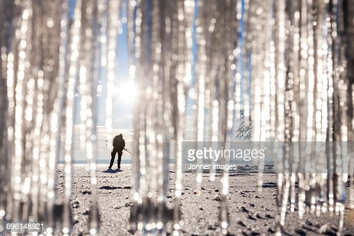 Silhouette of person on beach. icicles on foreground