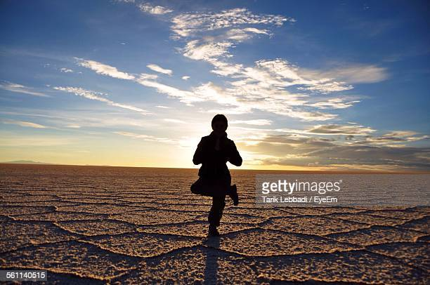 Silhouette Of Person Practicing Yoga On Salt Flat