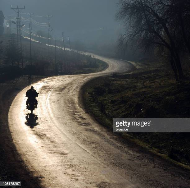 Silhouette of Person Riding Motorcycle on Foggy, Wet Road