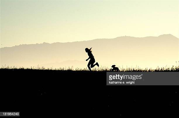 Silhouette of person running with small dog