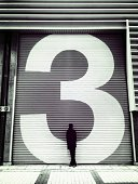 Silhouette of person standing against corrugated iron shutter
