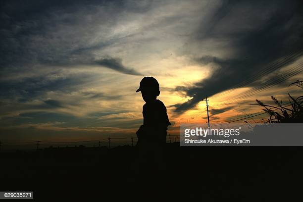 Silhouette Of Person Standing On Field Against Dramatic Sky