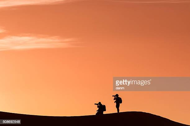 Silhouette of photographers in desert Sahara, Morocco'n