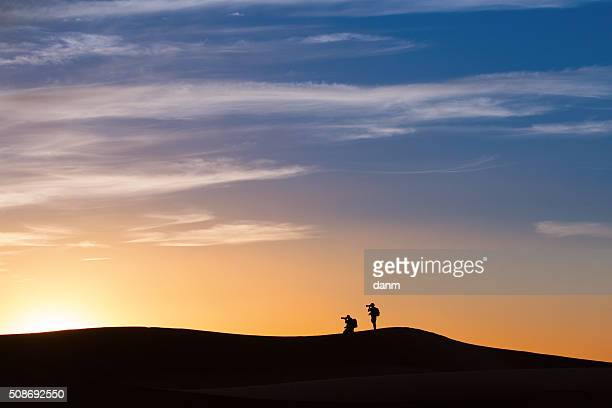 Silhouette of photographers in desert Sahara on sunset, Morocco