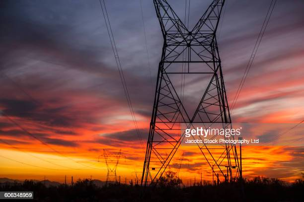 Silhouette of power lines against sunset sky