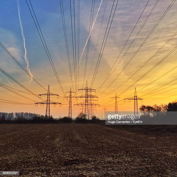 Silhouette Of Power Lines At Dusk Against Cloudy Sky