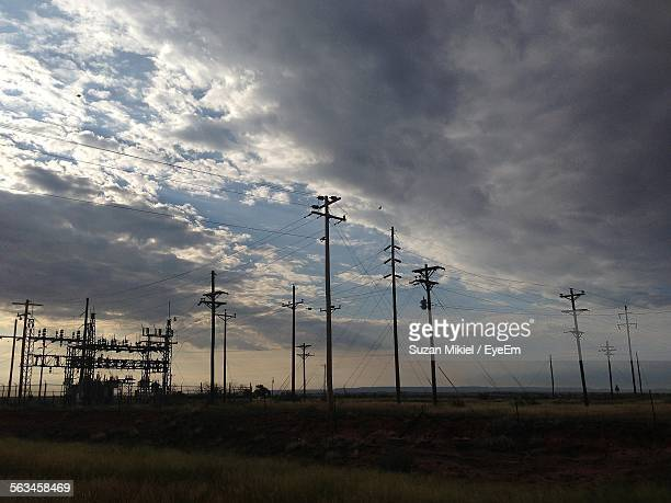 Silhouette Of Power Lines Under Cloudy Sky