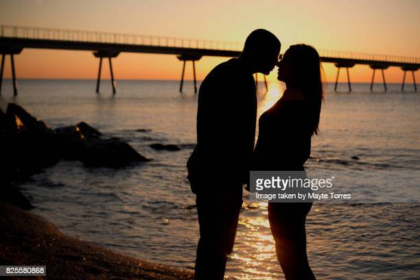 silhouette of pregnant couple at the beach kissing