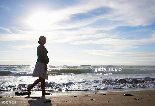 Silhouette of pregnant woman walking along beach.