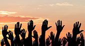 Silhouette Of Raised Hands Against The Dramatic Sky At Sunset