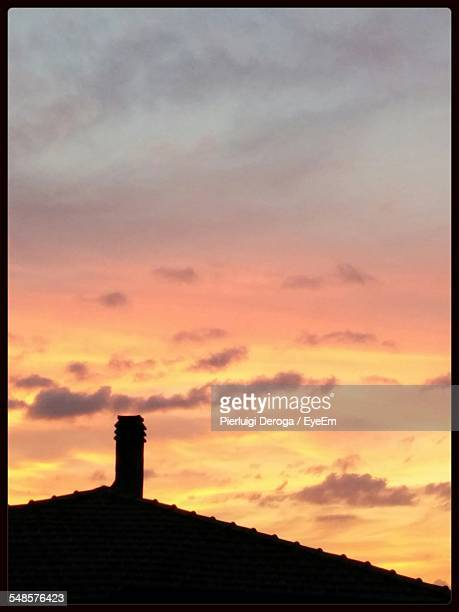 Silhouette Of Roof And Chimney At Sunset