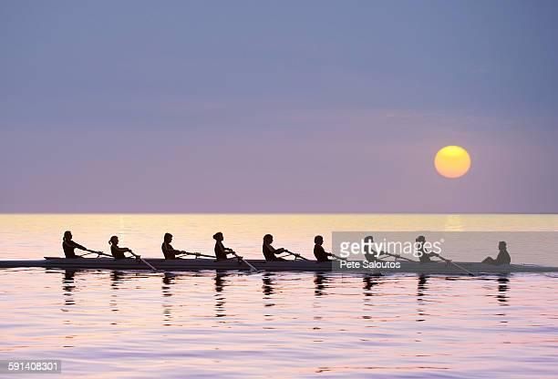Silhouette of rowing team practicing on still lake