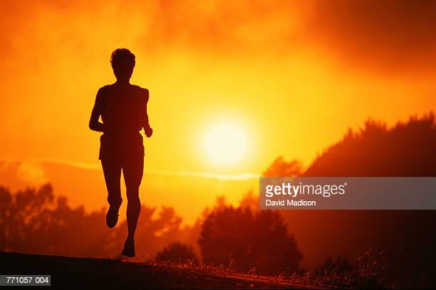 Silhouette of runner on road at sunrise