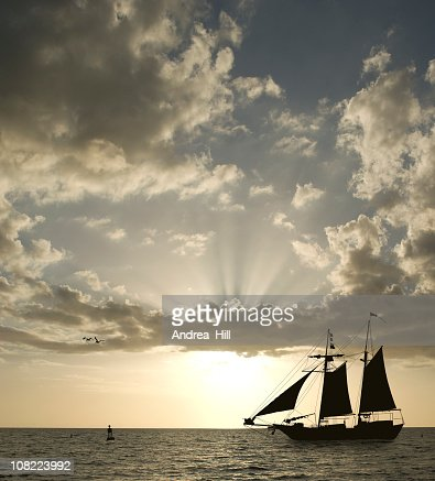 Silhouette of Sailboat on Horizon at Sunset