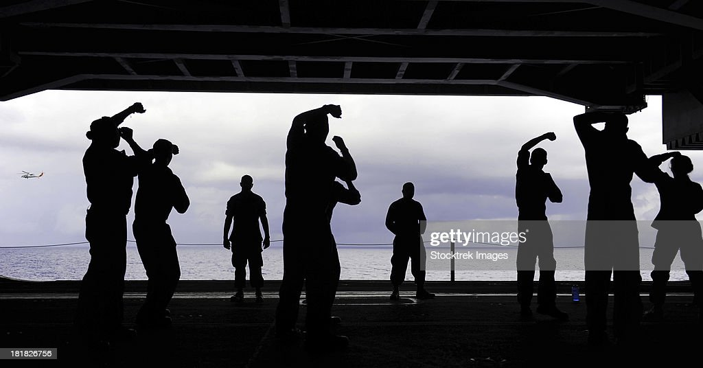 Silhouette of sailors in the hangar bay aboard USS George H.W. Bush.