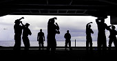 Silhouette of sailors in the hangar bay aboard USS George H.W. Bush.