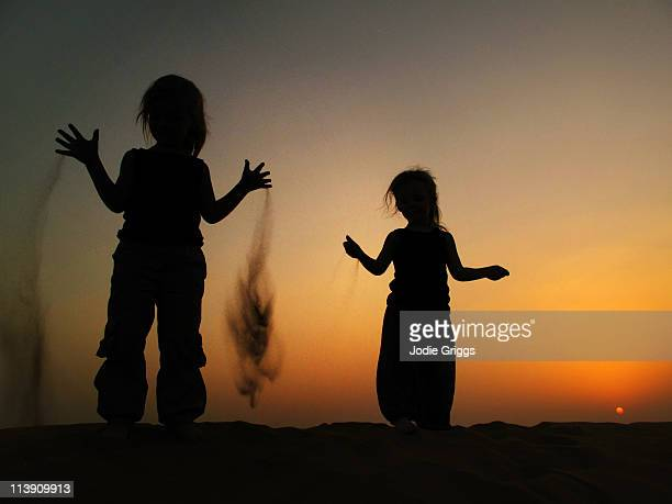 Silhouette of sand slipping through childs hand