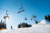 Silhouette of skier on snowy slope and low angle shot of a ski lift at ski resort in the mountains on a sunny winter day blue sky copyspace people riding top extreme activity sport recreation concept