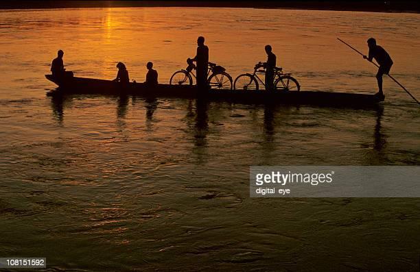 Silhouette kleines Boot transportieren Passagiere auf den Fluss bei Sonnenuntergang