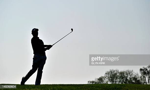 Silhouette of South African golfer Branden Grace watching his approach shot to the 1st green during the second round of the PGA Championship at...