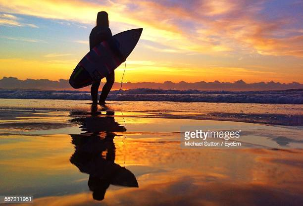 Silhouette Of Surfer Carrying Surfboard On Beach At Sunset