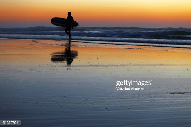 Silhouette of surfer on sunset