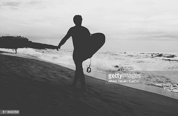 Silhouette of surfer walking with surfboard on beach