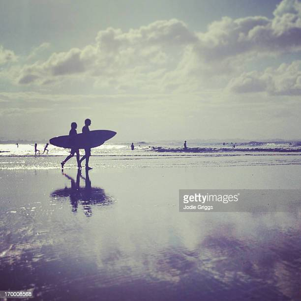 Silhouette of surfers walking along the beach