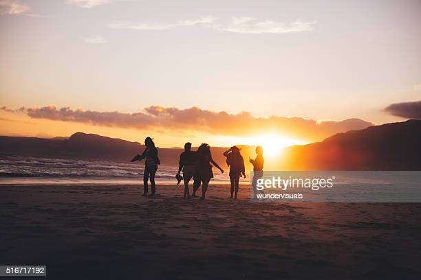 Silhouette of teen friends dancing on the beach at sunset