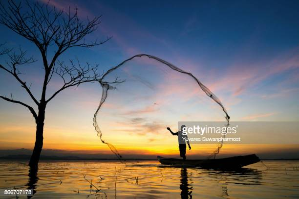 Silhouette of Thailand fisherman on wooden boat ,Thailand fisherman in action catching freshwater fish in nature river, Traditional fishermen at the sunset,Thailand