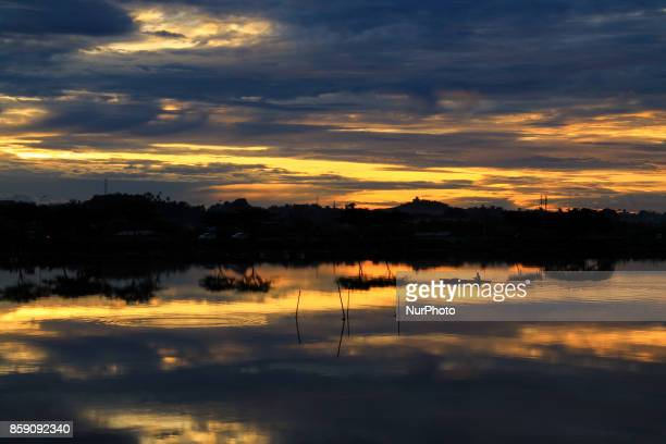 A silhouette of the fisherman are rowing a boat with a background of a sunset in the fishing village of Lhokseumawe on October 7 Aceh province...