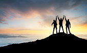Silhouette of the team on the peak of mountain. Sport and active life.