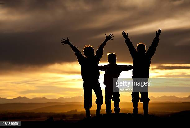 Silhouette of Three Happy Boys in The Mountains