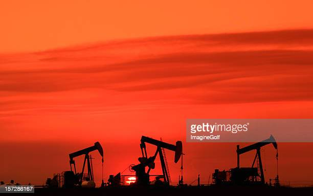 Silhouette of Three Oil Rigs Pumpjacks on the Prairie