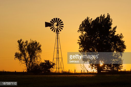 Silhouette of trees and windmill over a Prairie sunrise
