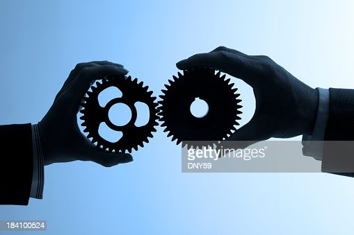 Silhouette of two business people holding gears