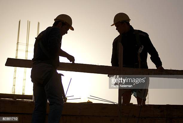 Silhouette of two construction workers holding a wooden plank, Salto, Uruguay