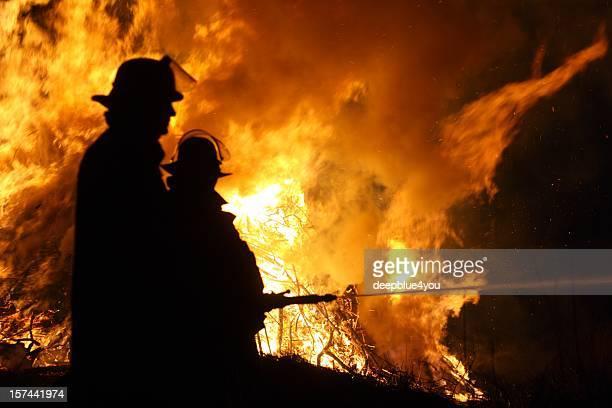 Silhouette von zwei Feuerwehrleute Löschen einer großen Feuer mit Wasser Schlauch bei Nacht