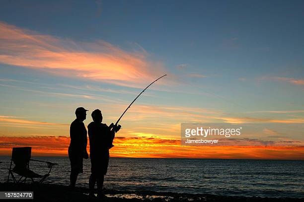 A silhouette of two men fishing at sunset