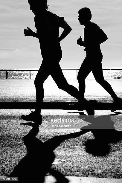 Silhouette of two men jogging together on a road, Nice, France