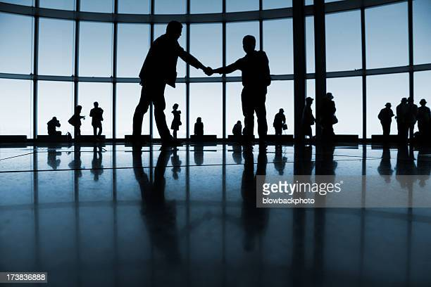 A silhouette of two men shaking hands in a business setting