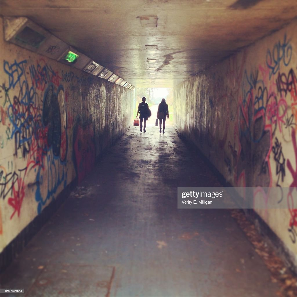 Silhouette of two people in an underpass